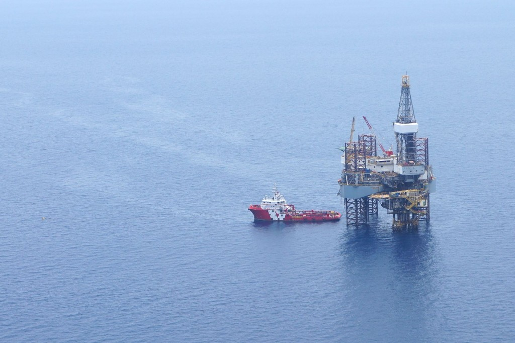 Offshore jack up drilling rig and supply boat in the middle of the ocean. Copyright:  / 123RF Stock Photo